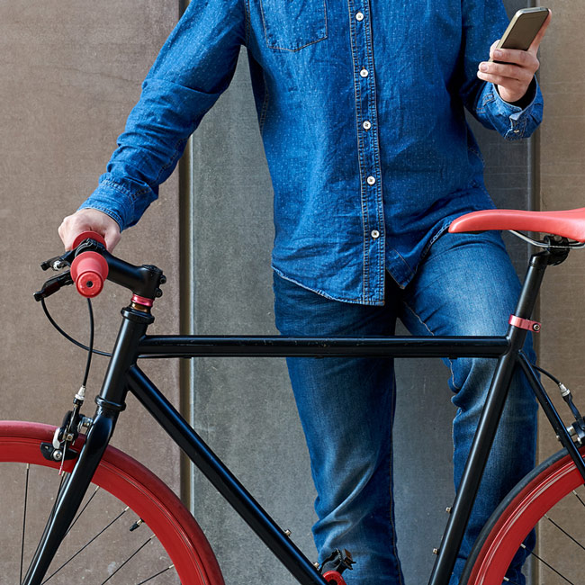 Man standing against a wall with his bike while looking at his smartphone
