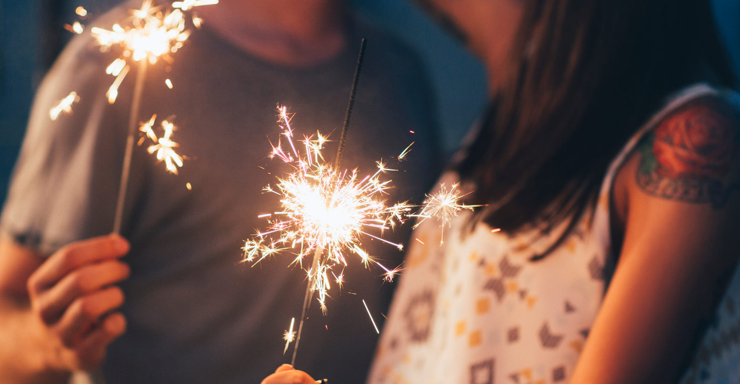 A young couple holding sparklers at night