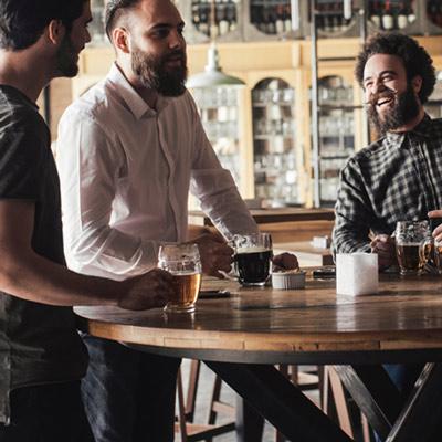 Three men talking and having drinks ata bar