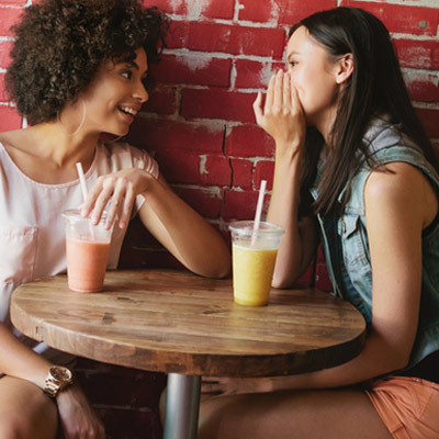 Two women talking amd drinking smoothies at a local cafe