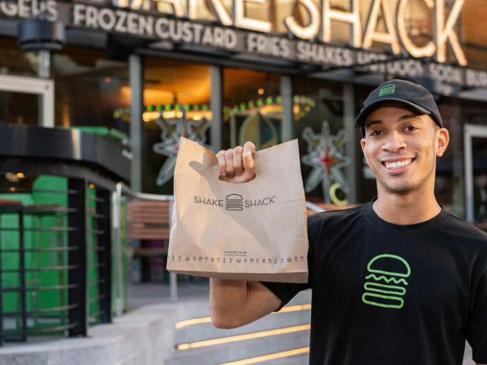 A smiling Shake Shack employee holding a take out bag