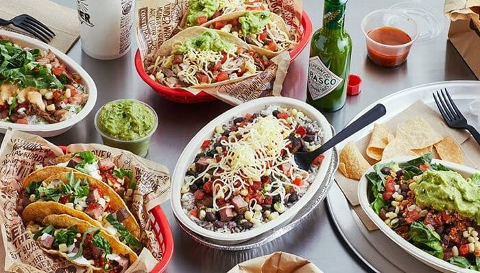 Plates of Chipotle burritos, tacos, and salad