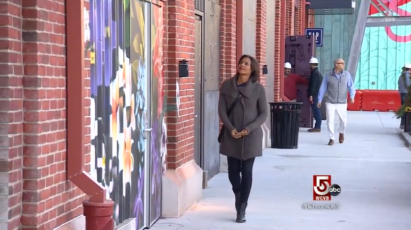 Woman walking down a sidewalk at Arsenal Yards