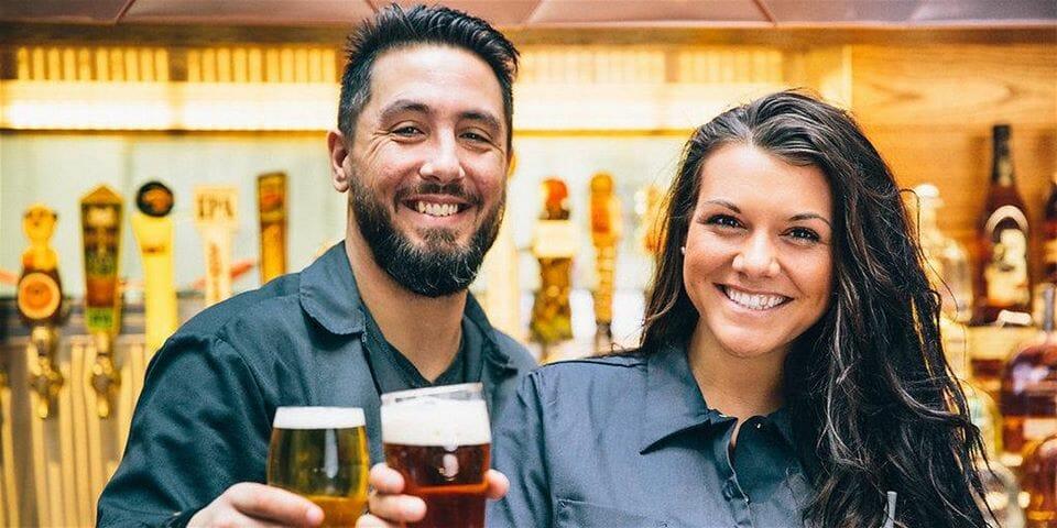 Friendly bartenders holding pints of beer