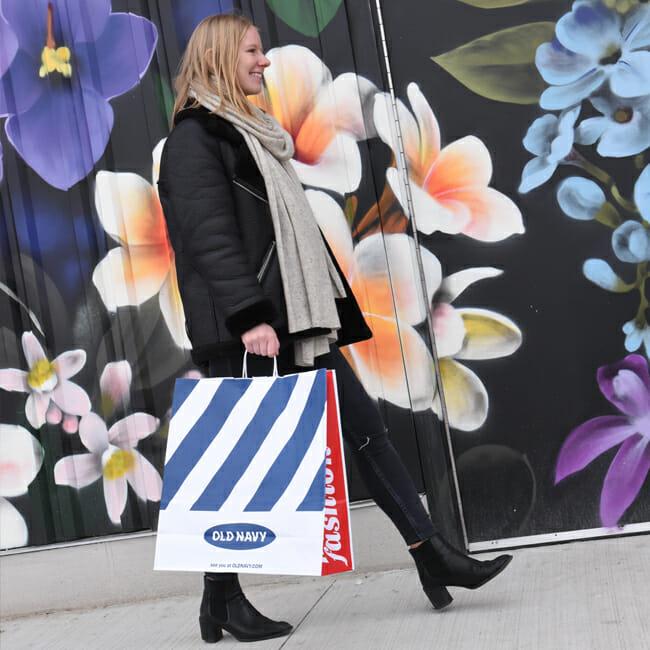 Woman walking down an Arsenal Yards sidewalk carrying an Old Navy shopping bag