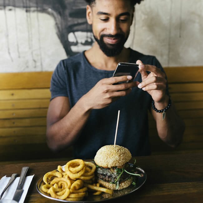 Man in a restaurant taking a picture of his meal with a smartphone