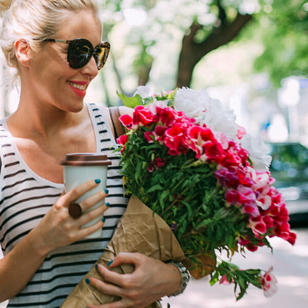A happy woman on a city street holding a bouquet of pink flowers and a coffee