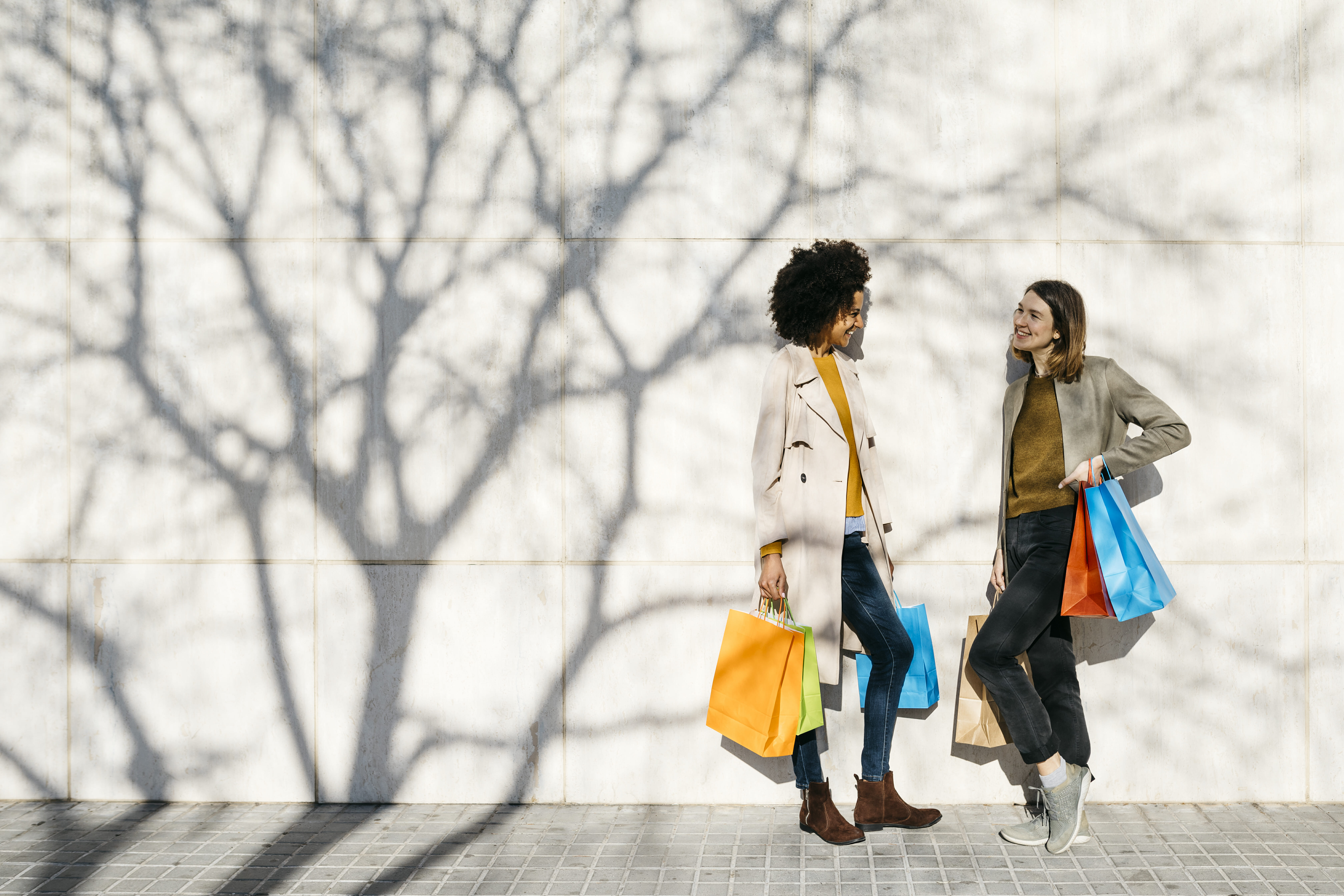 Two happy women with shopping bags standing at a wall talking