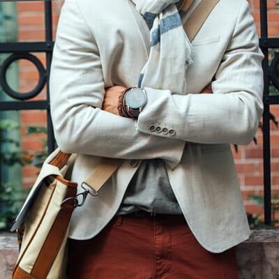 A man's torso wearing a fashionable blazer, a crossbody bag, and a classic watch