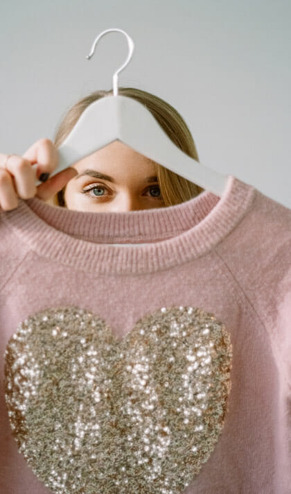 Woman holding a pink sweater on a hanger in front of her face. Her eyes are visible above the neck of the sewater.